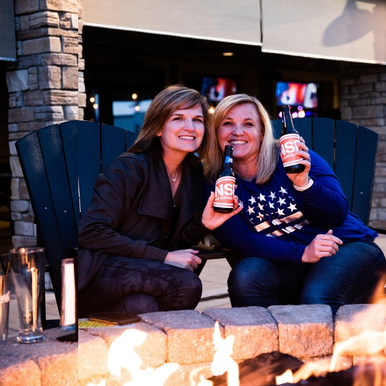 Two women sitting at a fire pit