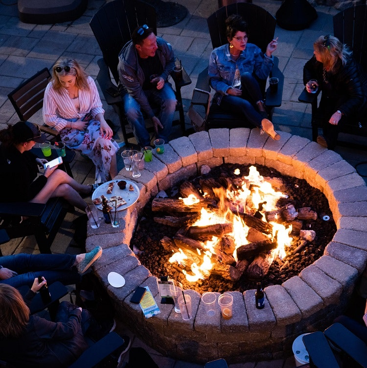 A group of people sitting around a fire pit