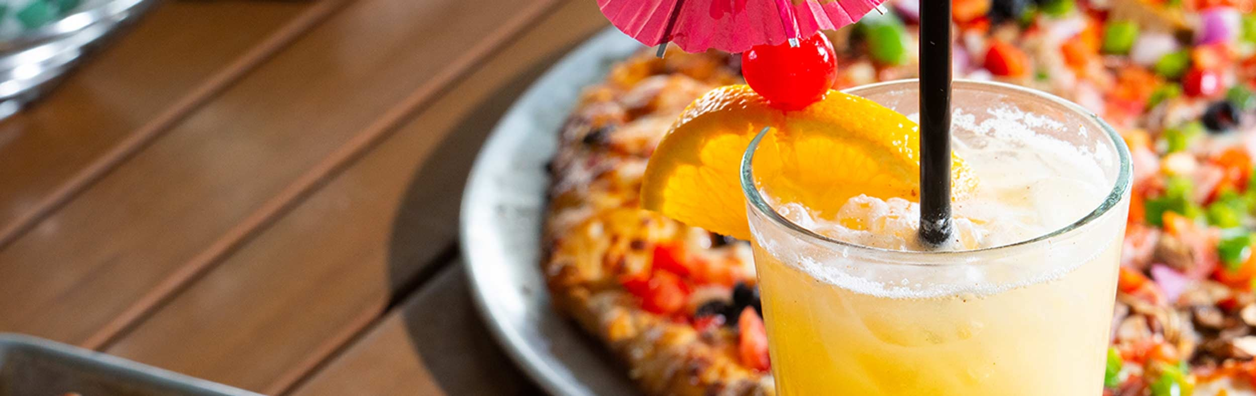 Drink with umbrella and pizza